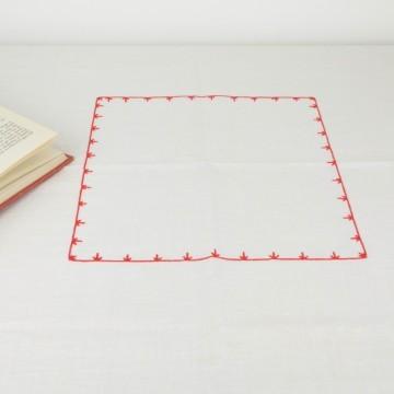 Pequeño mantel artesanal con detalle en rojo