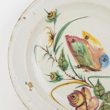 Plato o fuente antigua con mariposa